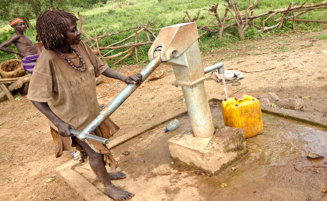 Hami pumps water from a new well built by DEC member World Vision