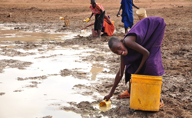 Girl collects watering from a muddy water hole in Kenya