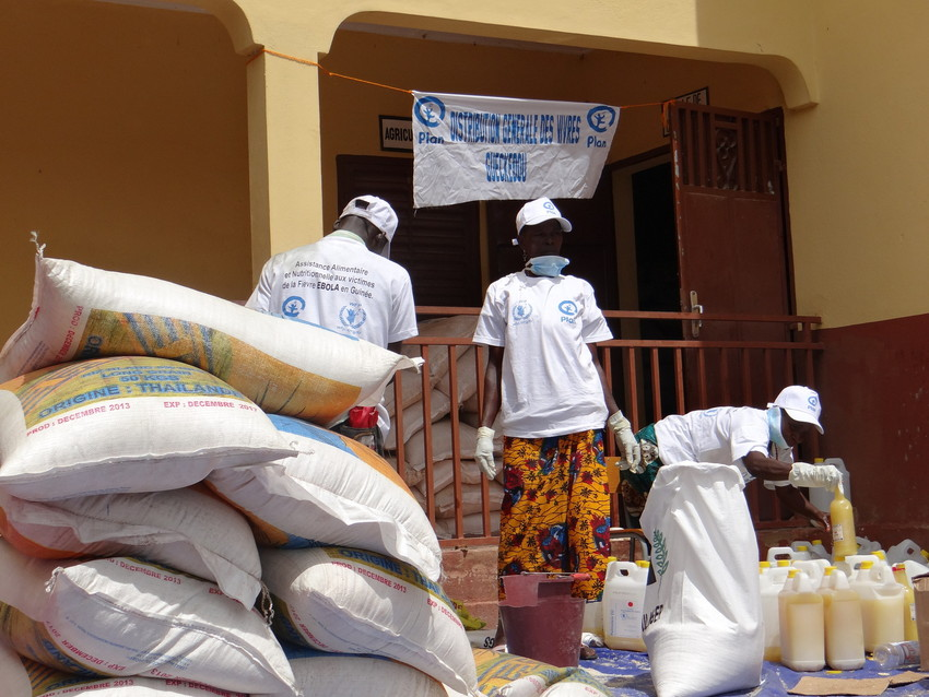 Plan staff prepare food packages at a distribution centre in Guinea