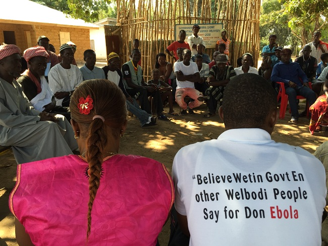 "Health education meeting in Sierra Leone run by CARE International. The t-shirt says: ""Believe what the government and health authorities tell you about how to stop Ebola""."