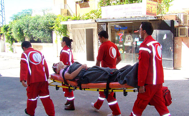 SARC (partner of DEC member British Red Cross) volunteers carrying stretcher in Homs