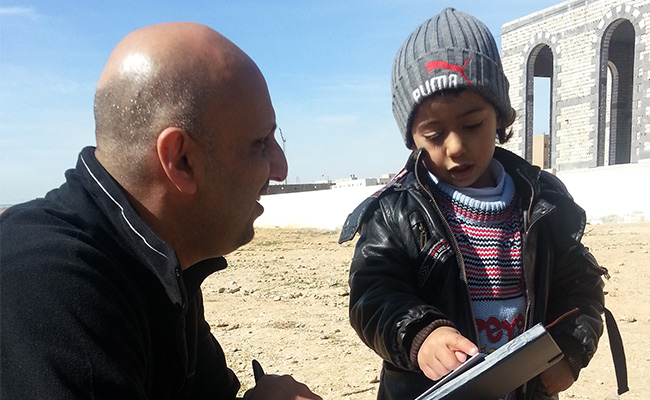 Syrian refugee child showing Saleh Saeed directions
