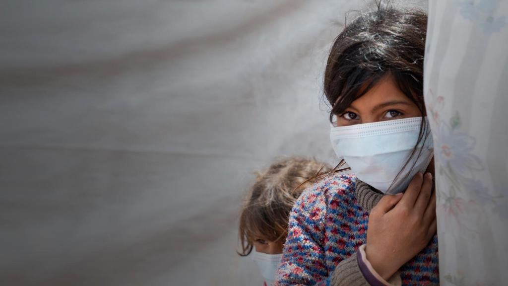A girl wearing a mask beside her family's tent at a displacement camp in Idlib, Syria
