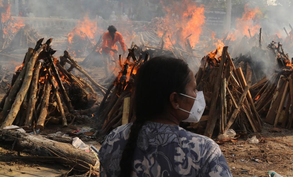A woman watches funeral pyres burn in New Delhi