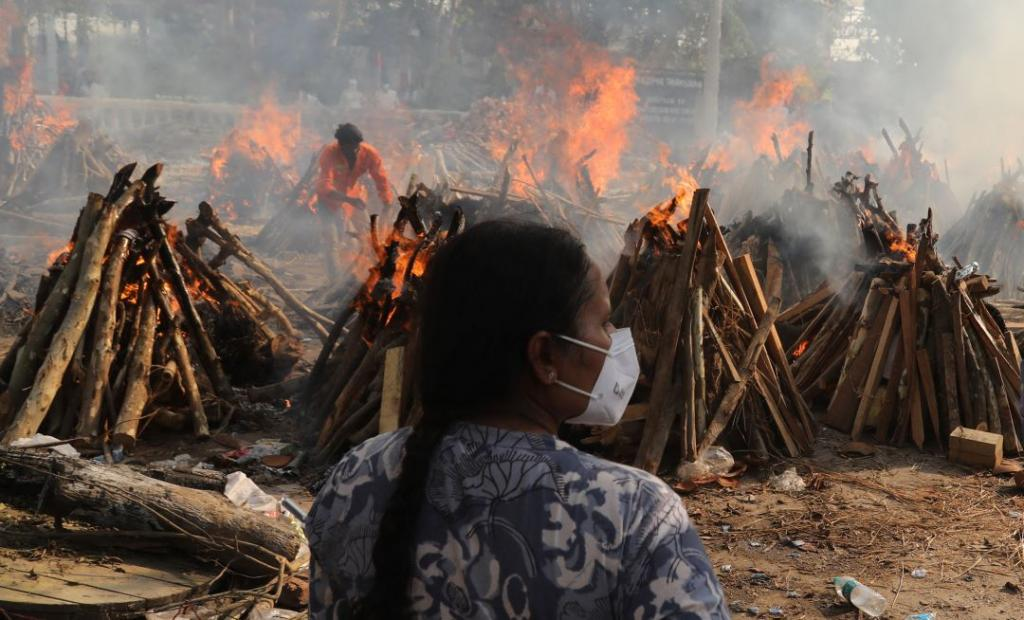 A family member looks on as several funeral pyres of those patients who died of COVID-19 disease burn up