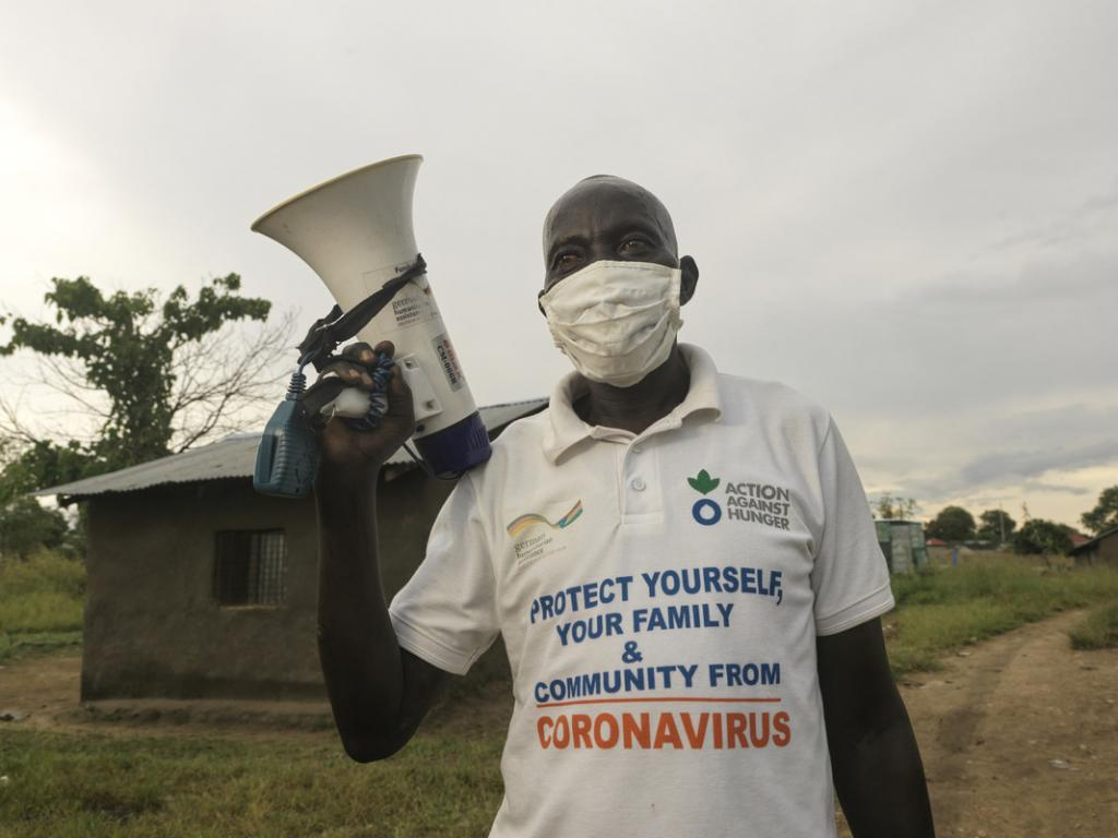 An aid worker carries a megaphone