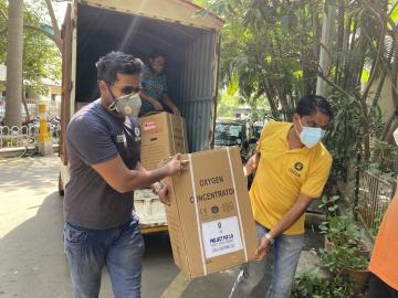 Oxfam staff unload an oxygen concentrator