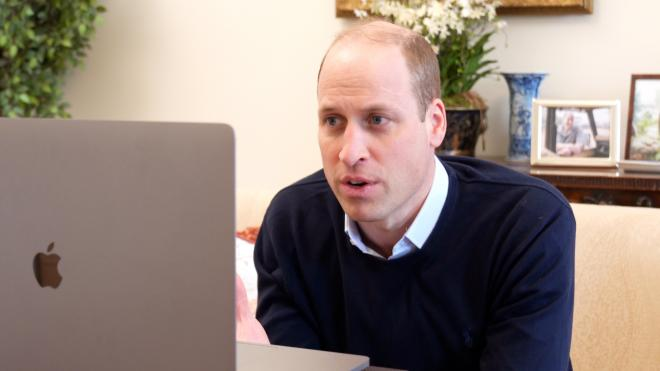 Prince William sits in front of a laptop