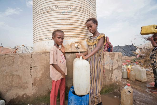 Two girls fill a jerry can at a water tank