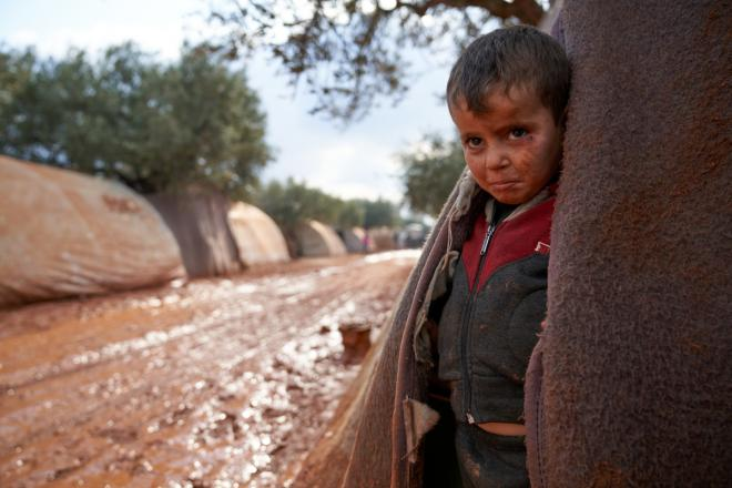 A boy stands at the entrance to a tent in a muddy camp in Syria