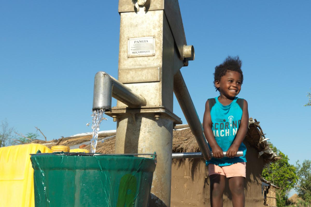 A girl uses a water pump restored with DEC funds after Cyclone Idai
