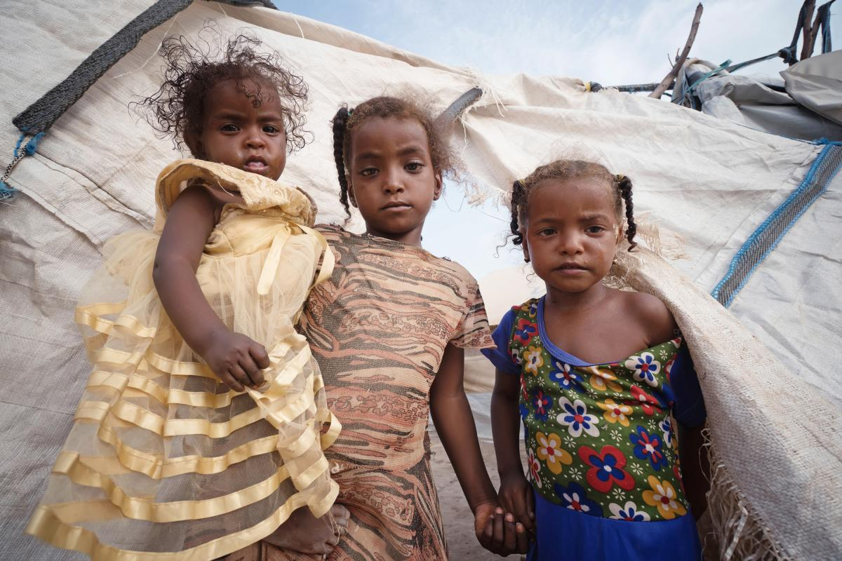 Three girls stand outside their tent in a displacement camp in Yemen